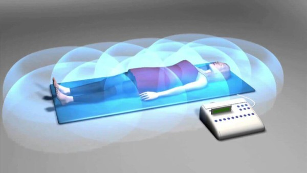 PEMF (Pulsed Electromagnetic Frequency) therapy. You can tell it works because the cartoon frequencies surround the patient.