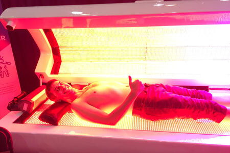 Andrew LaTour testing a red light therapy bed at a biohacking conference